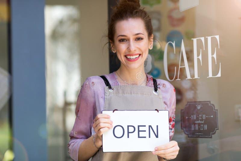 La tenencia de la mujer abierta firma adentro el caf? fotos de archivo libres de regalías