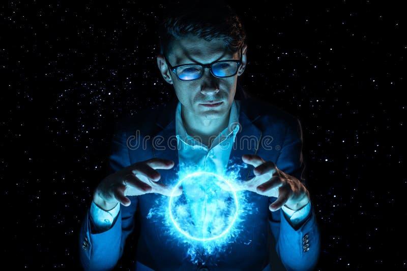 La tenencia del hombre de negocios del hombre entrega una esfera azul del plasma que brilla intensamente Predicción y previsión fotos de archivo libres de regalías