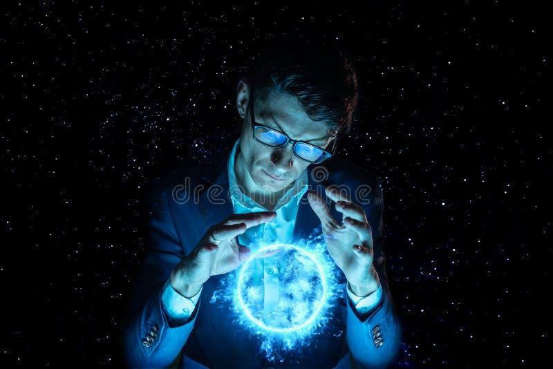La tenencia del hombre de negocios del hombre entrega una esfera azul del plasma que brilla intensamente Predicción y previsión imagen de archivo