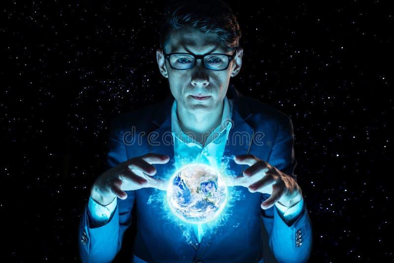 La tenencia del hombre de negocios del hombre entrega una esfera que brilla intensamente azul bajo la forma de tierra del planeta fotografía de archivo