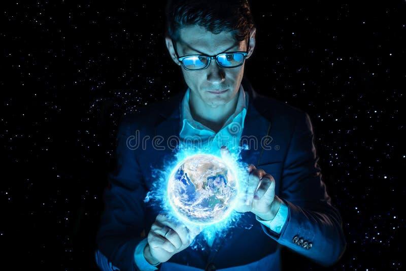 La tenencia del hombre de negocios del hombre entrega una esfera que brilla intensamente azul bajo la forma de tierra del planeta fotos de archivo libres de regalías