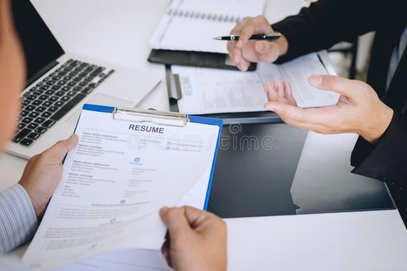 La tenencia del patr?n o del reclutador que lee un curriculum vitae durante alrededor coloquio su perfil del candidato, patr?n en fotografía de archivo