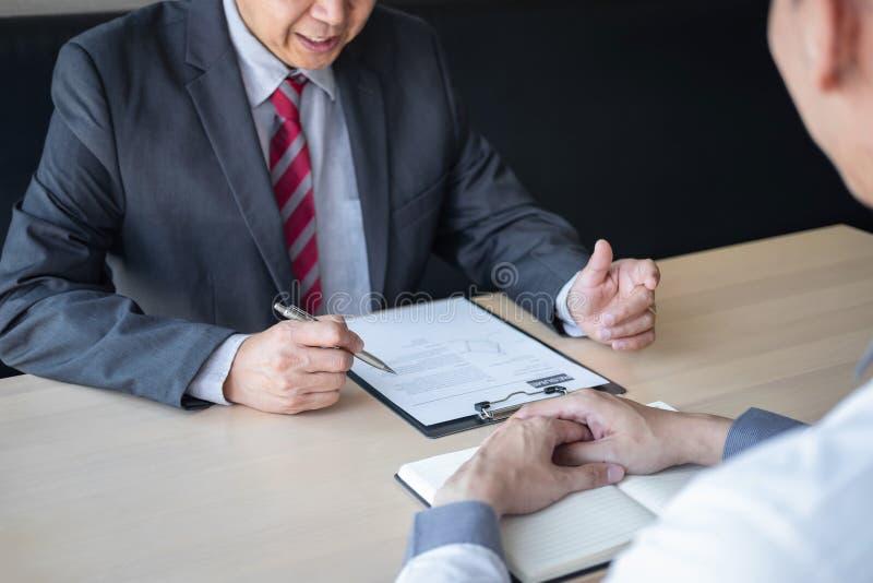 La tenencia del patr?n o del reclutador que lee un curriculum vitae durante alrededor coloquio su perfil del candidato, patr?n en imagenes de archivo
