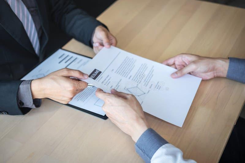 La tenencia del patr?n o del reclutador que lee un curriculum vitae durante alrededor coloquio su perfil del candidato, patr?n en foto de archivo