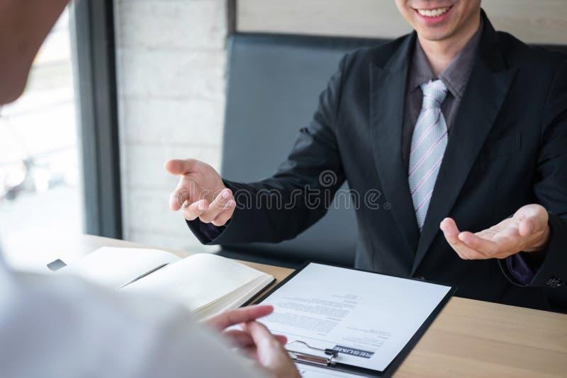 La tenencia del patr?n o del reclutador que lee un curriculum vitae durante alrededor coloquio su perfil del candidato, patr?n en fotos de archivo