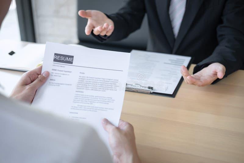 La tenencia del patr?n o del reclutador que lee un curriculum vitae durante alrededor coloquio su perfil del candidato, patr?n en fotografía de archivo libre de regalías