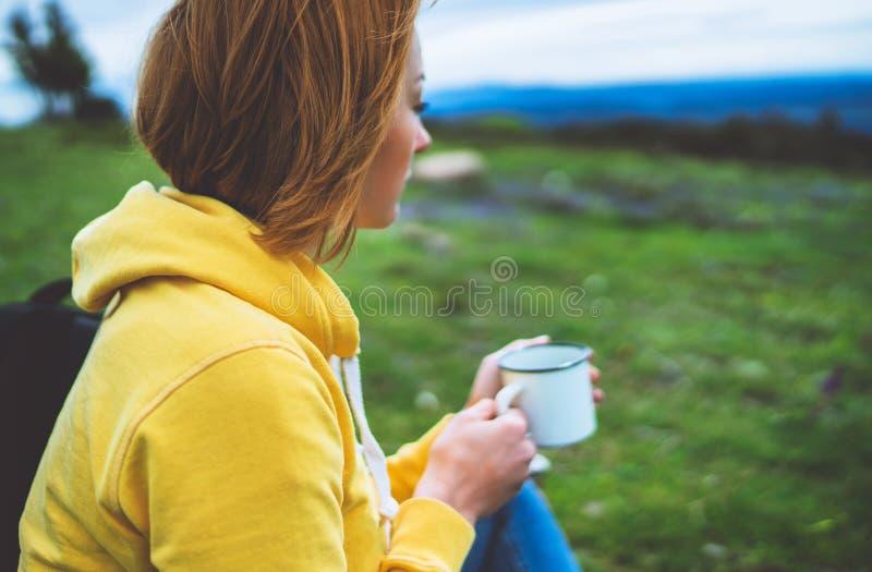 La tenencia feliz de la muchacha en taza de las manos de té caliente en hierba verde en la opinión superior del parque de natural imagen de archivo