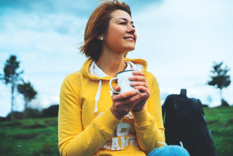 La tenencia feliz de la muchacha de la sonrisa en taza de las manos de té caliente en hierba verde en parque de naturaleza del ai imágenes de archivo libres de regalías