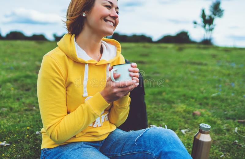 La tenencia feliz de la muchacha de la sonrisa en taza de las manos de t? caliente en hierba verde en parque de naturaleza del ai fotos de archivo