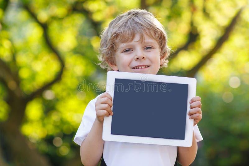 La tenencia feliz sonriente del pequeño niño hace tabletas la PC, al aire libre foto de archivo
