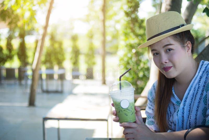 La tenencia hermosa de la mujer heló el té verde, fondo borroso, coffe fotos de archivo libres de regalías