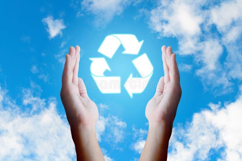 La tenencia joven asiática de la mano recicla el icono y las nubes y cielo de la naturaleza fotografía de archivo libre de regalías