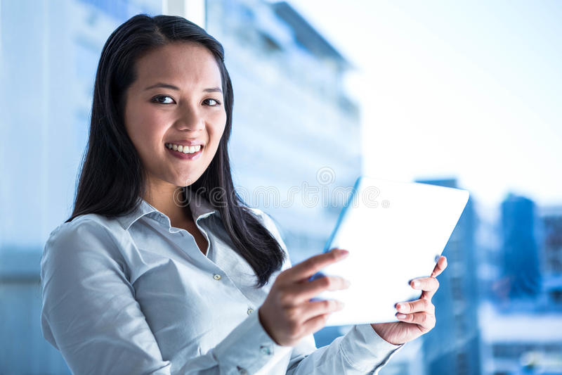 La tenencia sonriente de la empresaria hace tabletas y mirada de la cámara imágenes de archivo libres de regalías