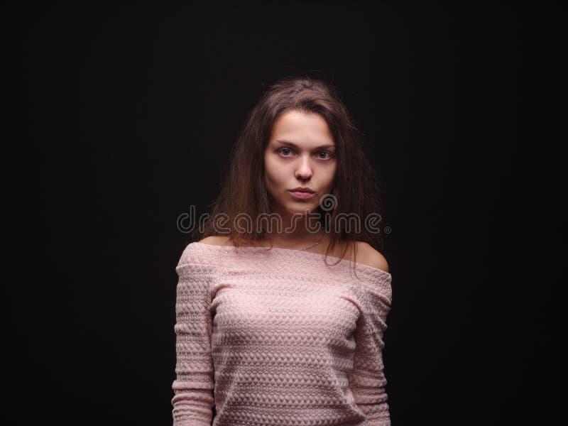 La tenencia triste de la mujer enredó el pelo en el fondo negro Penacho del pelo en una mano del ` s de la muchacha Concepto de l imagenes de archivo
