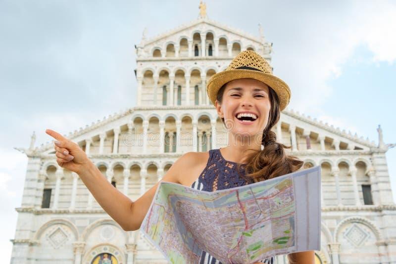 La tenencia turística sonriente de la mujer traza y señalando en Pisa imagen de archivo