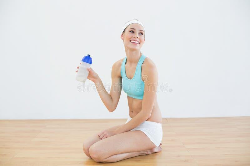 La tenuta d'uso degli abiti sportivi della giovane donna esile mette in mostra la bottiglia fotografia stock