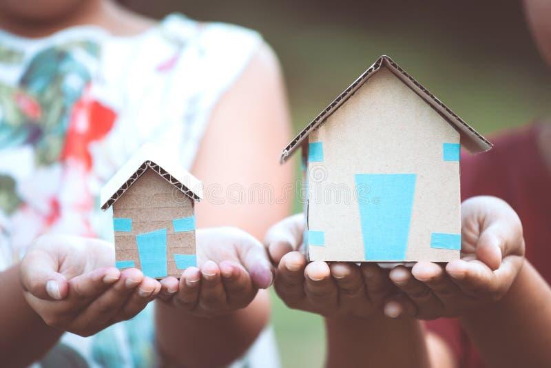La tenuta del genitore e del bambino incarta la casa in mani fotografia stock libera da diritti