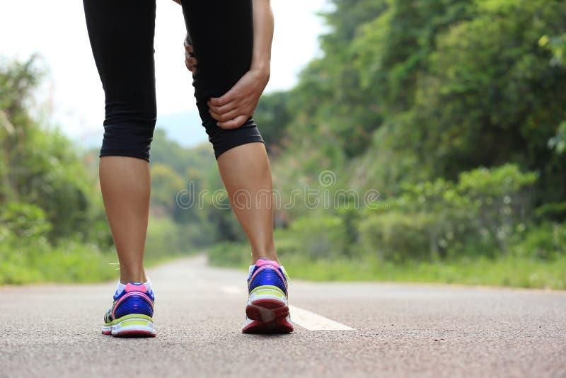 La tenuta del pareggiatore della donna i suoi sport ha danneggiato la gamba fotografia stock