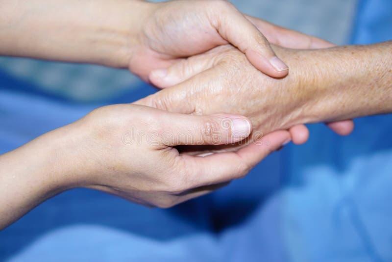 La tenuta del paziente senior delle mani commoventi o anziano asiatico della donna della signora anziana con amore, cura, aiutant fotografia stock