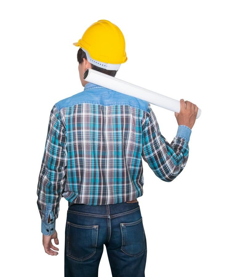 La tenuta dell'ingegnere ha rotolato la costruzione dei modelli sulla spalla e la testa indossa la plastica gialla del casco di s immagine stock