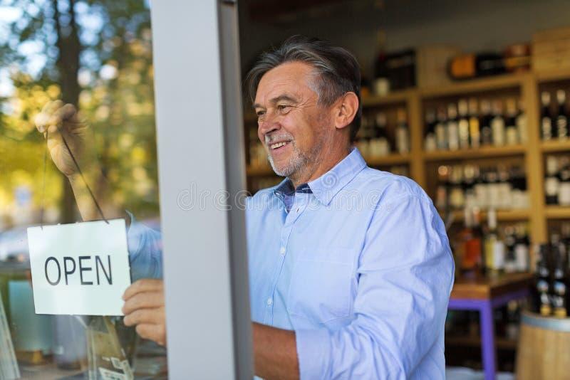 La tenuta dell'uomo aperta firma dentro il negozio di vino fotografia stock