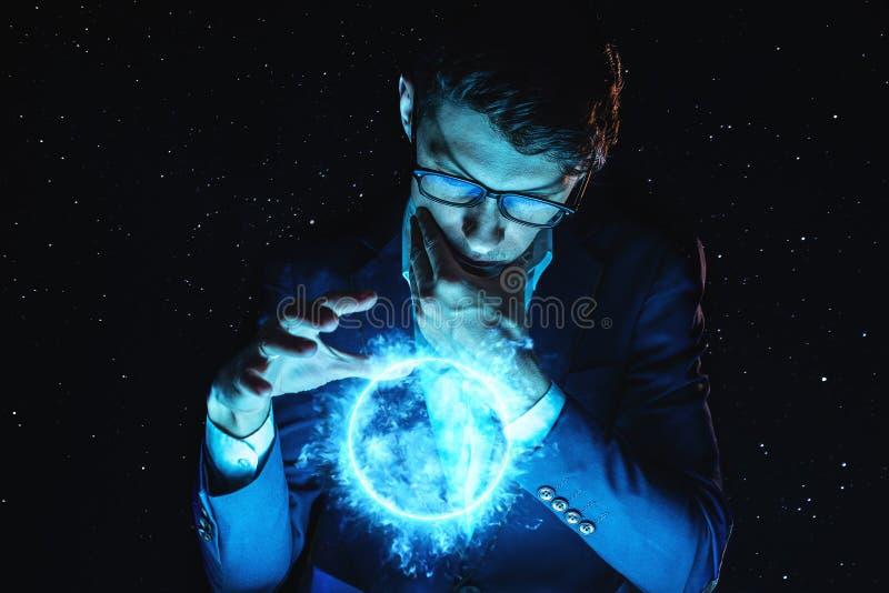 La tenuta dell'uomo d'affari dell'uomo consegna una sfera d'ardore blu del plasma Previsione e previsione magiche in affare e fin fotografie stock libere da diritti