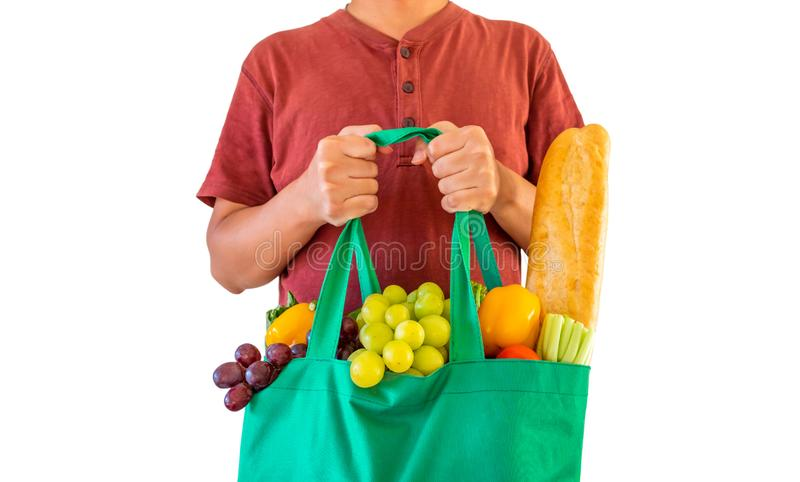 La tenuta dell'uomo reen il sacchetto della spesa riutilizzabile riempito di frutta fresca e di prodotto pieni della drogheria de immagine stock libera da diritti
