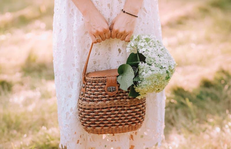 La tenuta della borsa del vestito dalla ragazza fiorisce il bianco del mazzo immagine stock