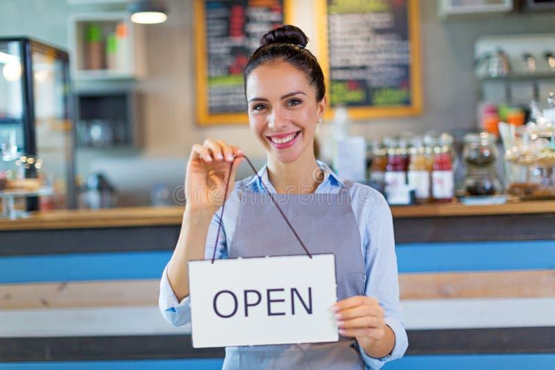 La tenuta della donna aperta firma dentro il caffè immagini stock libere da diritti
