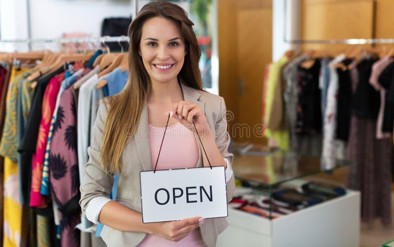 La tenuta della donna aperta firma dentro il negozio di vestiti immagine stock libera da diritti