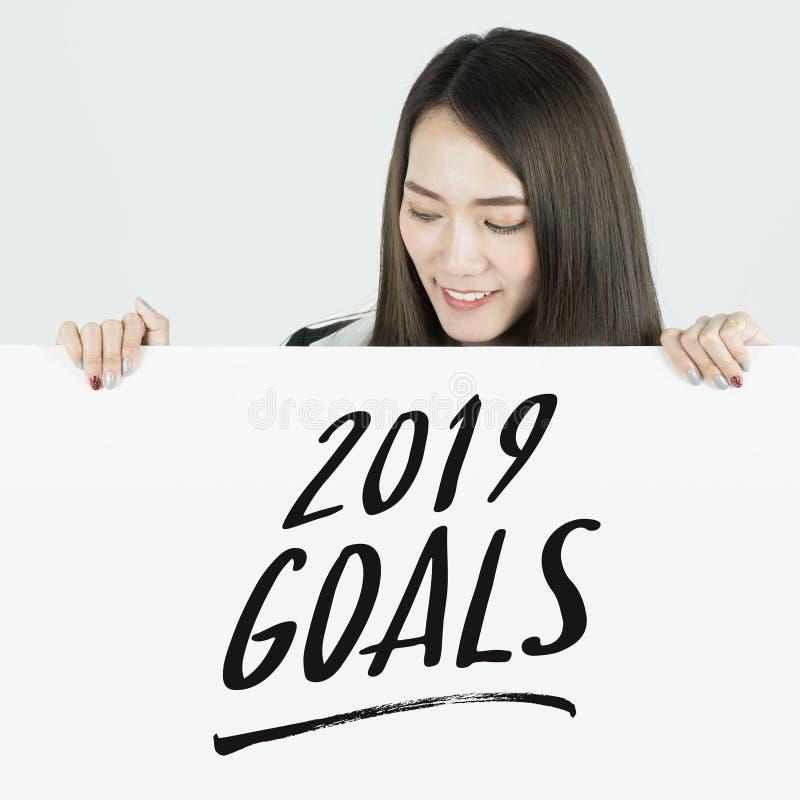 La tenuta della donna di affari affigge 2019 scopi firma immagini stock