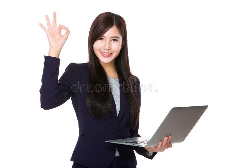 La tenuta della donna di affari con il computer portatile ed il segno giusto gesture immagini stock