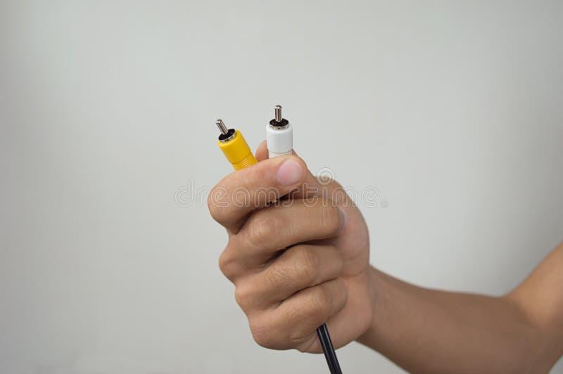 La tenuta della mano solleva il giallo ed il bianco con il crick fotografia stock