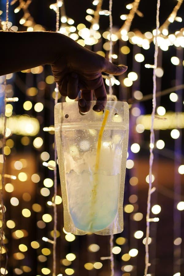 La tenuta della mano vede attraverso la bevanda del recipiente di plastica al festival immagine stock libera da diritti