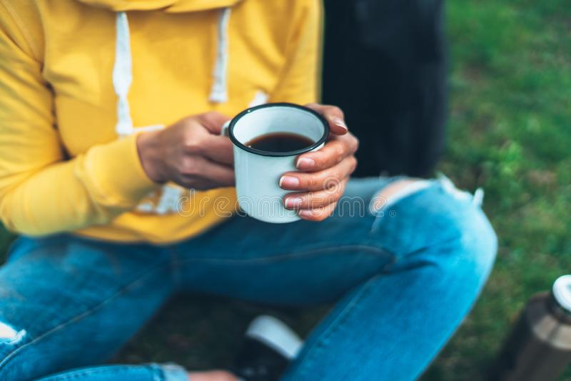 La tenuta della ragazza di vista superiore in tazza delle mani di tè caldo su erba verde nel parco naturale di aria aperta, bei p immagini stock libere da diritti