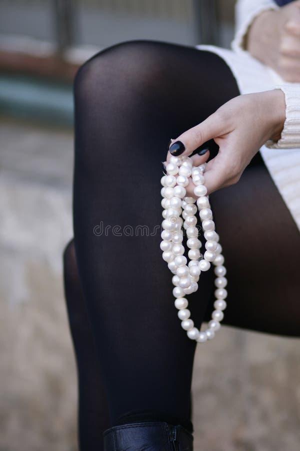 La tenuta femminile della mano imperla lo stillife all'aperto di modo fotografie stock libere da diritti