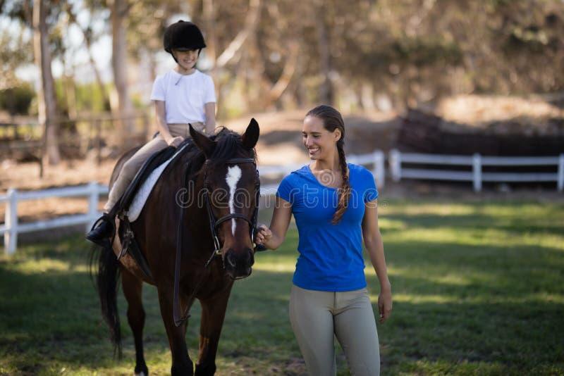 La tenuta femminile sorridente della puleggia tenditrice mette un freno a mentre sorella che si siede sul cavallo immagini stock