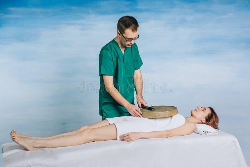 La terapia di una donna con un tamburino Il massaggiatore maschio fa i metodi non tradizionali di medicina fotografia stock libera da diritti