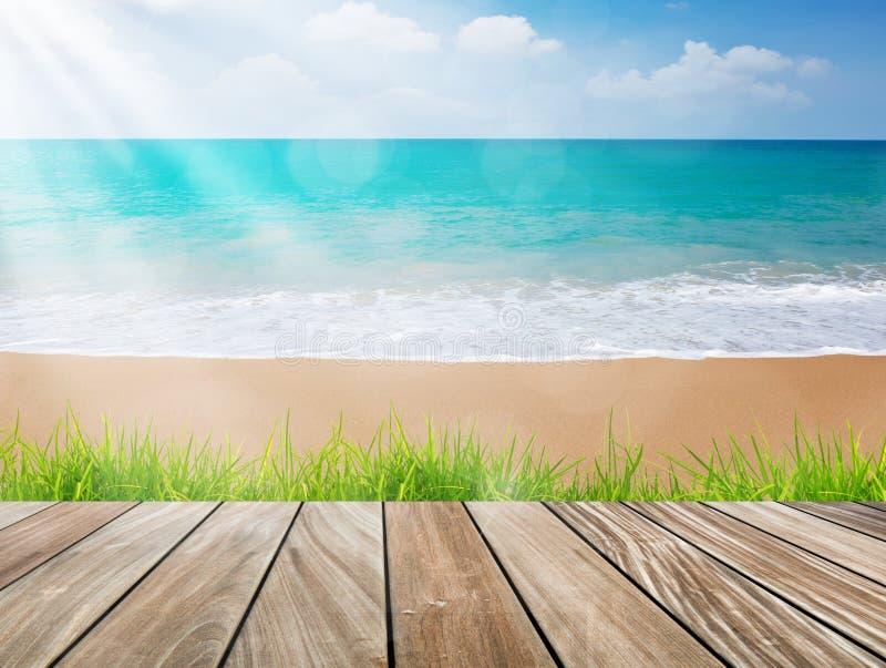 La terrasse en bois sur la plage avec l'herbe verte et le soleil s'allument image stock