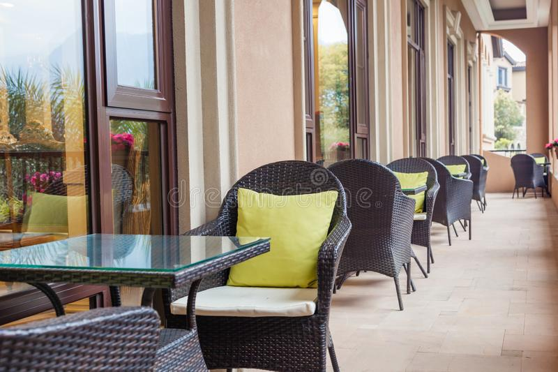 La terrasse extérieure de café avec des tables et des wickerchairs photographie stock libre de droits