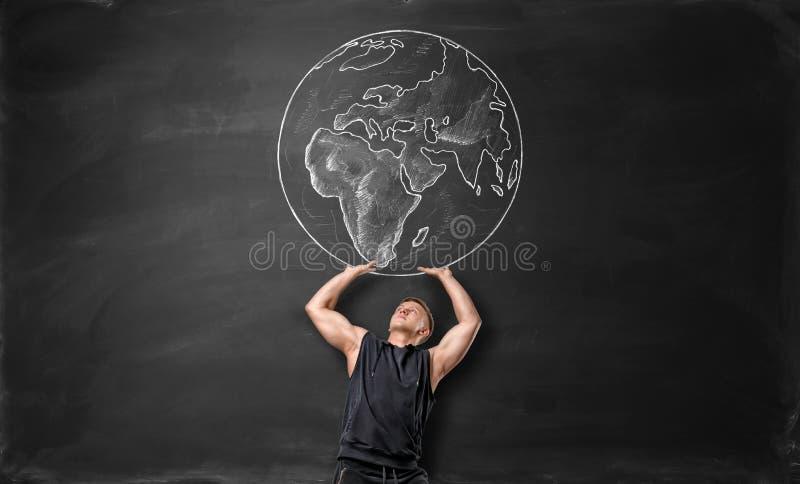 La terre décrite sur le tableau noir et l'homme sportif agissant comme il le tient au-dessus de se images stock