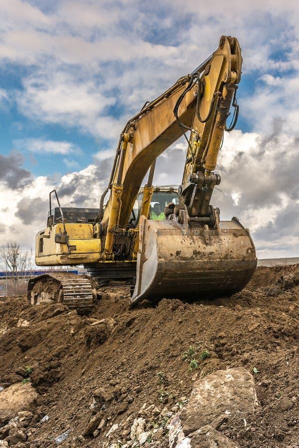 La terre de chargement d'excavatrice pour effectuer des travaux de règlement d'une route photographie stock libre de droits