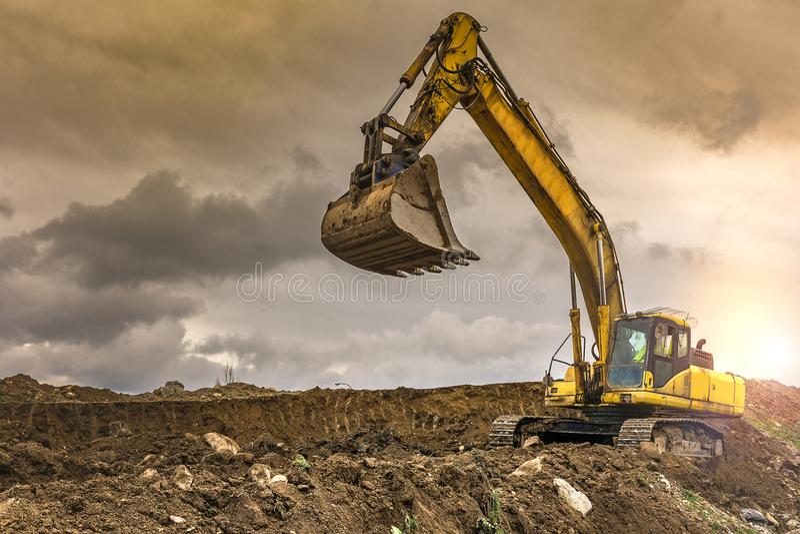 La terre de chargement d'excavatrice pour effectuer des travaux de règlement d'une route photos stock