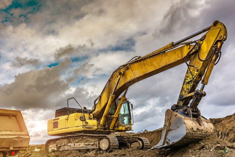 La terre de chargement d'excavatrice pour effectuer des travaux de règlement d'une route photo stock