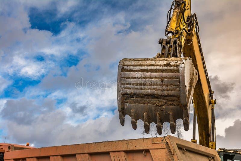 La terre de chargement d'excavatrice pour effectuer des travaux de règlement d'une route images stock