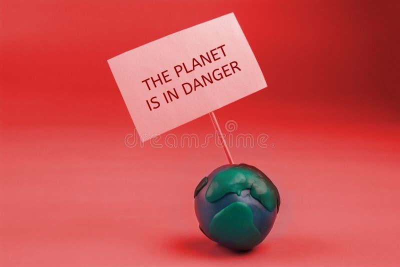 la terre de planète dans le concept de danger la terre tenant une bannière images stock