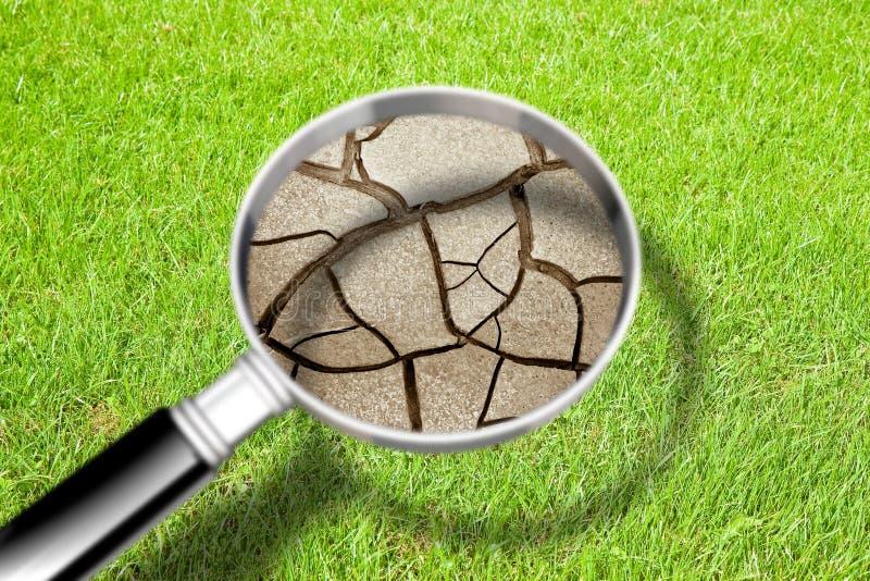 La terre fendue vue une loupe - les effets de la s?cheresse - image de concept image stock