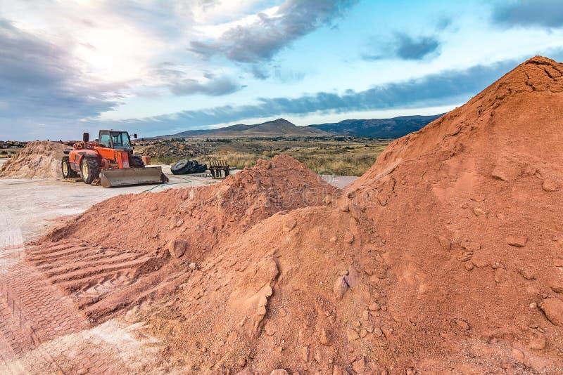 La terre mobile d'excavatrice sur des travaux de construction d'une route photo stock