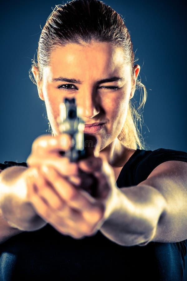 La terroriste dangereuse de femme s'est habillée dans le noir avec une arme à feu dans son Han images libres de droits