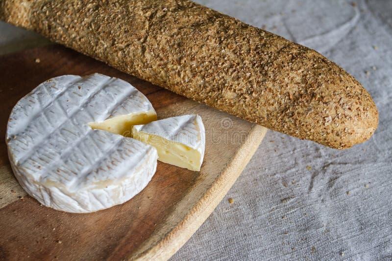 La testa del formaggio svizzero del camembert e di un pezzo triangolare di formaggio su un bordo di legno e di baguette del grano fotografia stock